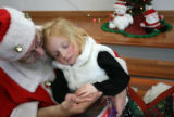 MJM425  Ava Jaksha, 3, holds the hand of Santa Claus played by Richard Gibboney (cq) as he...
