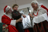 MJM140  Anton Kiwimagi, 5, opens a present under the watchful eyes of Santa Claus and Mrs. Claus,...
