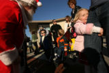 MJM604  Elie Musfeldt, 3, hugs her mother, Kerry Musfeldt's leg (cq) as they visit Santa Claus...
