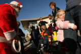 MJM606  Elie Musfeldt, 3, hugs her mother, Kerry Musfeldt's leg (cq) as they visit Santa Claus...