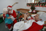 MJM675  Jasmine Drummond, 5, claps her hands as she says goodbye to Santa Claus and Mrs. Claus,...