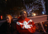 (0433) Barbara Burdue and Joey Higgins, ride the bus past Christmas decorations on 16th street...