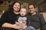 Maria, and Gabriel Trejos pose with their 13 month old son, Elijah    in the living room of their...
