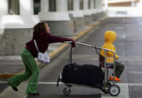 (0102) Alexa Gilmore, 9, pushes her brother A.J. Gilmore, 4, at DIA in Denver., Colo., on Tuesday,...