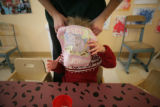 Annika Sandberg, 2 (cq) has her bib put on before eating lunch at the YWCA of Boulder County at...