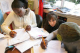 Teacher Linda Schwartz works with Sudanese students Mary Nakiru, left, and Susan Loriho, right, in...