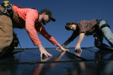 Sam Mason (cq) and Steve Carroll (cq) (L-R) of Namaste Solar Electric install Sunpower 225 watt...