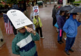 Wayne Young (cq), (left bottom), 50, of Boulder, Colo., uses his protest sign in the likeness of a...