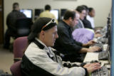 Mike Ortega , front, searches for jobs with other job seekers at the Denver Workforce Center at...