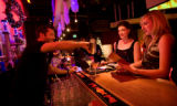 (Denver, Colorado, Dec. 6, 2008) Bartender Tim Herring serves martinis to Melissa Dundas and...
