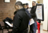People wait in line to access a computer to search for jobs at the Denver Workforce Center at...