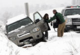 A man helps a woman out of her vehicle on westbound I-70 just west of the Lookout Mountain exit....