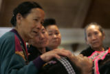 Yee Vang, left, carresses the forehead of 64-year-old Ying Yang, as other family members and...