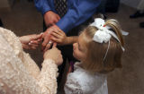 (Vernal, Utah) Alicia Padigimus, 5, daughter of Amber Swain, looks at Jonathan's hands after he...