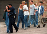 RMN164-4-20-99-Denver,Co.--A law enforcement official comforts an unidentified student as they are...