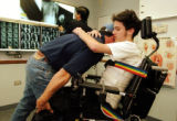 Rick Castaldo helps his son, Richard, get adjusted in his wheelchair during a visit to a doctor. ...