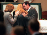 RMN187-4/25/98-Dee Dee Fleming is comforted by her husband, Don Fleming as they view their...