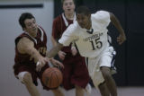 #15 Terrance Brockman (cq) of Denver Lutheran dribbles past #4 Joel Hegarty of Faith Christian on...