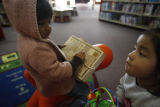 SR(079)  In front, three-year-old Karla Escamilla, of Commerce City looks up at the books while...