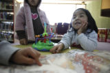 SR(107)  In front, three-year-old Karla Escamilla, of Commerce City looks up at her sister while...