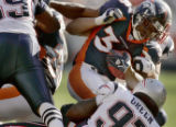 Denver Bronco's running back, MIke Anderson,middle, pushes for a first down being pulled down by...