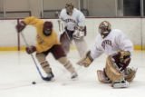 An unidentified University of Denver Pioneers player attempts to get a puck past goalie Peter...
