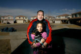 0294 Douglas Ries, 40, holds his daughter Maya Ries, 10, in their front yard in a cul-de-sac that...