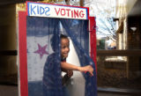 Ryan Herrera, 5, of Elizabeth, Colo., emerges from a voting booth after casting his ballot during...