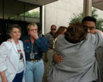 Victim family members Darlene Welch and Rudy Guzman, right, hug as Blanche Tomlin, far left, and...