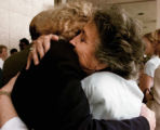 Victim family member Blanche Tomlin, right,  hugs an unidentified person outside of the U.S....