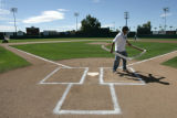 (0922) Efran Tellez finishes up the lines on home plate before the Colorado Rockies play the...