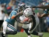 The Denver Broncos' Tatum Bell (#26, RB) slips through the tackle of the Jacksonville Jaguars'...