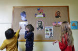 Children from Lincoln Elementary School pass by a mural with Abraham Lincoln's image as they...