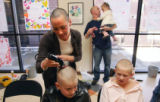 (353) Fifth grade teacher Jesica Harrington (cq), shaves the head of Bobby Rexroat as Davis Meyer,...