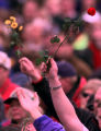 RMN124-DENVER,CO.- 4-25-99-Mourners raise their flowers to the sky while listening to Christian...