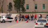 RMN183-20-99-Denver,Co.-A group of freed students and faculty run from Columbine High School in...