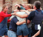 RMN166-4-20-99-Denver,Co.--Reunited students embrace after being rescued and  lead away  through...
