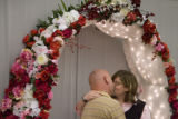 DM0214  Brandi and Michael Thelen kiss under the wedding arch at the Office of the Clerk and...