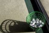 Golf balls sit in a basket near the putting station at Tiger's golf school located at 10041 E....