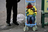 Three year old Durango Richardson tries to stay warm while waiting with is father, Marty...