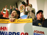 Craig MacNaughton, left, cheers as Democratic presidential candidate John Edwards talks to voters...
