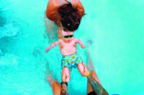 Six-month-old Travis Farnum takes a dip in the Congress Park swimming pool with his parents, Gina...