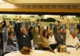 Republican voters raise their hands in support of Mitt Romney for precinct 260 at Campus Middle...