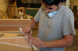 R.J. Butler, a Craftsman at Avalon Acoustics, prepares a speaker for veneer at the company's...