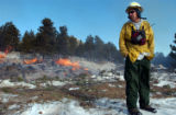 Fuel Specialist Doug Watry stands in front of a traditional pile burn at the Moraine Park...