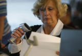 County clerk, for Morgan County, Connie Ingmire looks over a ballot that she had just scanned at...