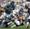 The Denver Broncos' Jake Plummer (#16, QB) gets sacked by the Jacksonville Jaguars' Reggie Hayward...