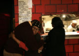 [339] Ethel Allen (cq) gets a huge hug good-bye from longtime patron Reggie Moore (cq), on the...