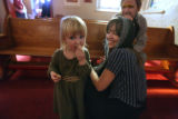 Taisiya Rubtsova, 2 gets some of the communion breadas her mother Kira Rubtsova and father...