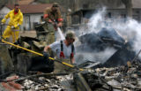 (PG0990)  Local firefighters work to extinguish a hot spot on April 16, 2008 the day after a fatal...